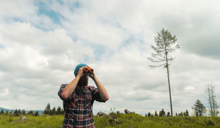 Low angle view of man looking through binoculars on field against sky