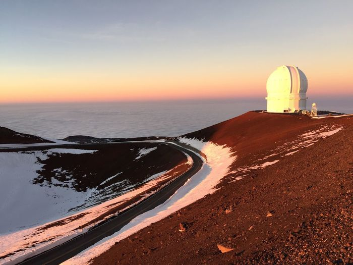 Mauna Kea Observatory On Volcanic Mountain By Cloudscape Against Sky During Sunset