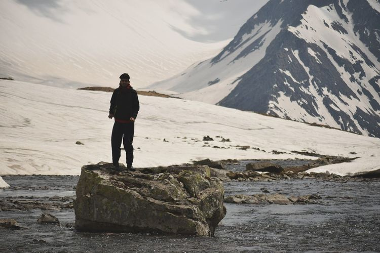Full length of man standing on rock against snowcapped mountains