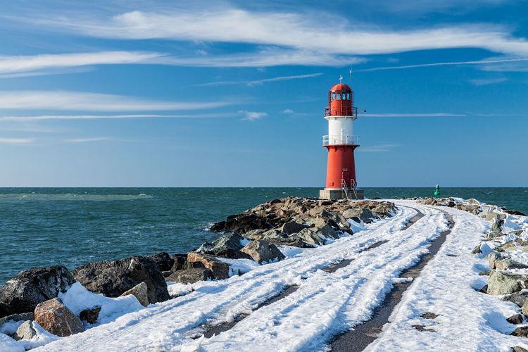 Lighthouse on beach against sky