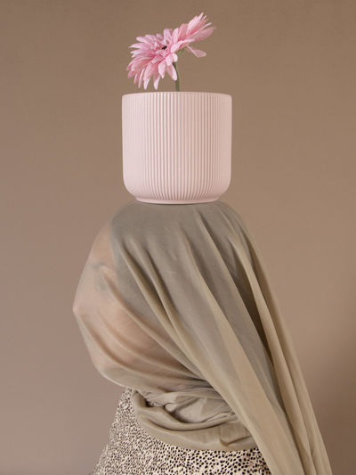 Side view of woman under scarf with flower pot on head against beige background