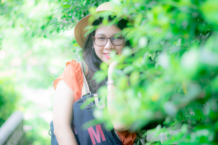 Portrait of woman smiling while standing by plants