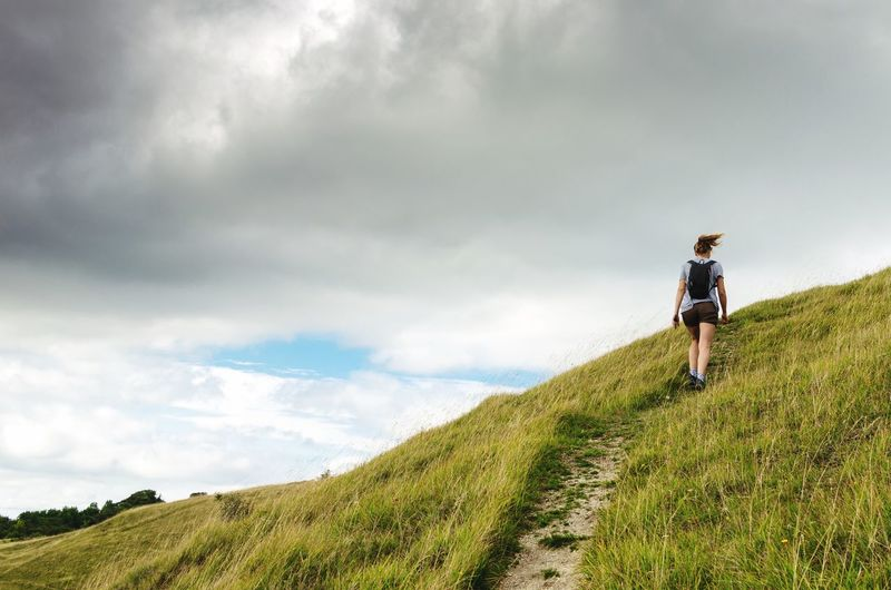 """""""Footsteps I cannot see. But I know you're with me."""" Active Woman Path Footpath Hill Countryside Summer Backpack Backpacking Hiker Hiking Adventure Grass Windy Cloud - Sky Sky Leisure Activity Real People Lifestyles Hiking Full Length Women Grass Beauty In Nature Non-urban Scene Adventure Adult Rear View Nature Walking"""