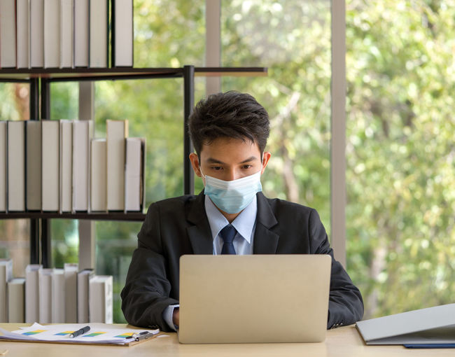 Man with mask using laptop at table in office