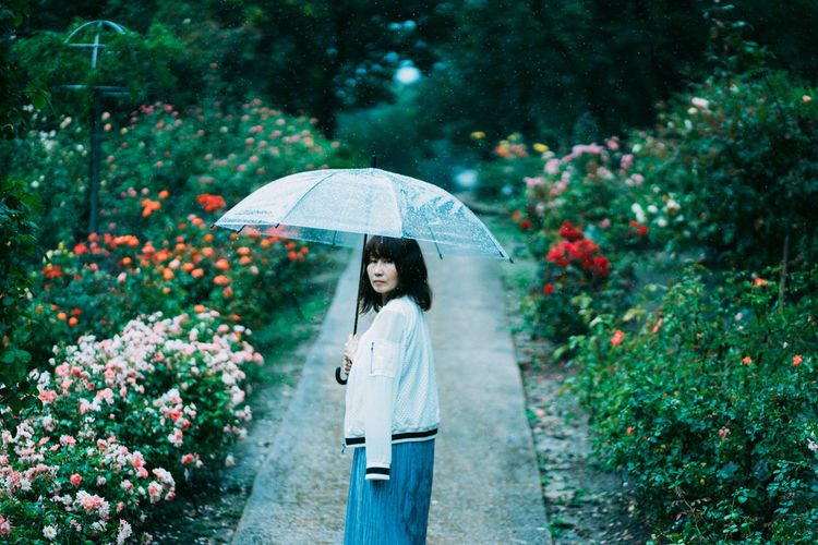 Woman holding umbrella standing by plants during rainy season