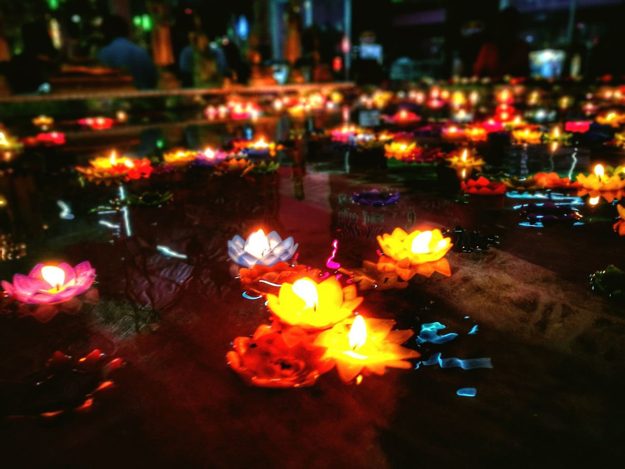 flame, burning, illuminated, night, candle, glowing, heat - temperature, tea light, no people, flower, outdoors, spirituality, nature, water, city