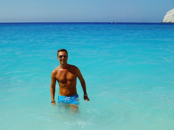 Portrait of shirtless man standing in sea against sky on sunny day