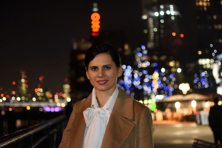 Portrait of smiling young woman in illuminated city at night