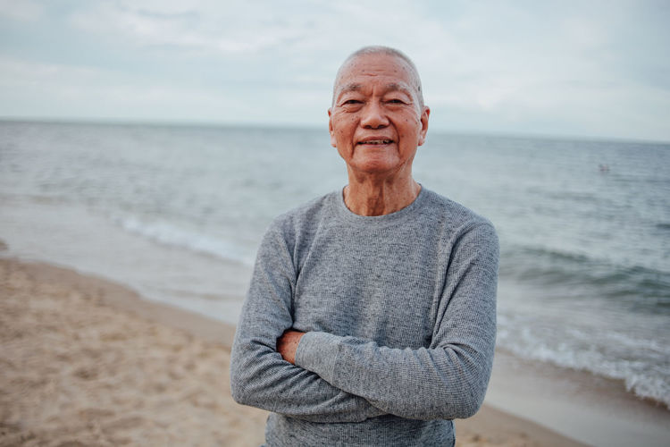 Portrait of senior man with arms crossed standing at beach against sky during sunset