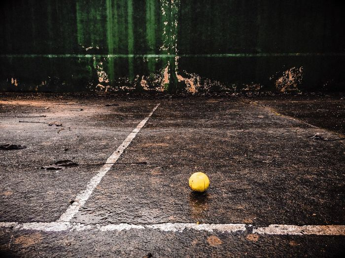 Tennis Ball On Wet Ground Against Wall