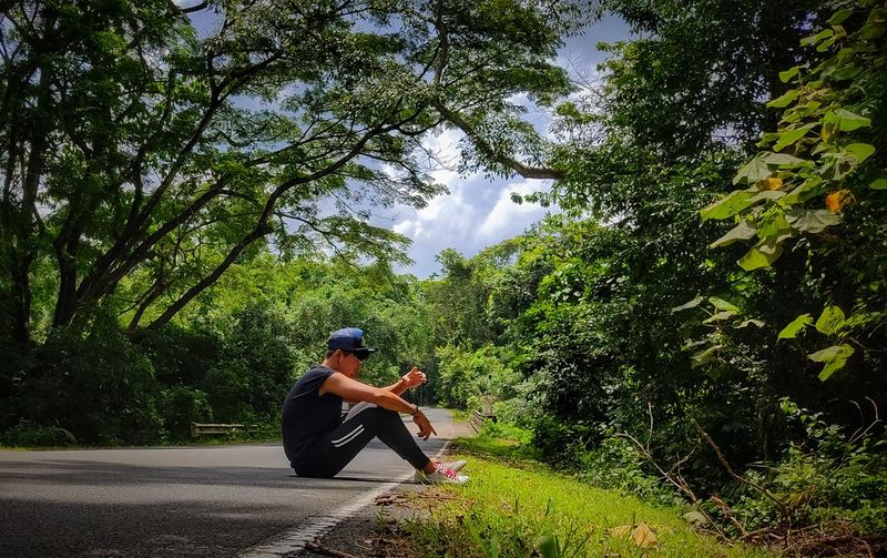 Side view of man sitting in forest