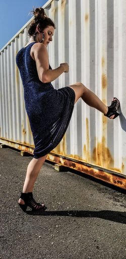Woman kicking cargo container