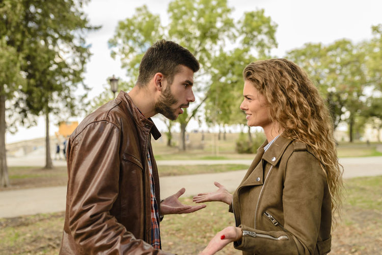 Young couple having a debate in the public park Bonding Casual Clothing Couple - Relationship Day Emotion Focus On Foreground Hairstyle Outdoors Plant Positive Emotion Real People Side View Standing Togetherness Tree Two People Waist Up Women Young Adult Young Men Young Women