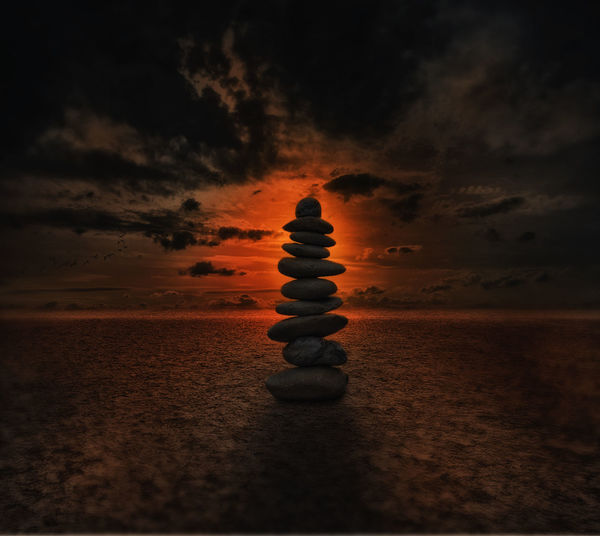 Stacked rocks at beach against cloudy sky at sunset