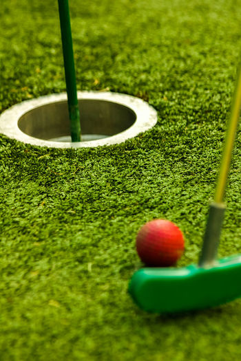 About To Win Artificial Floor Ball Childhood Close-up Color Contrast Family Day Out Focus On Background Grass Green And Red Green Color Make My Day Metal Miniature Golf No People One Last Time Plastic Grass Putting Green Red Ball Selective Focus Sport Successful Winner