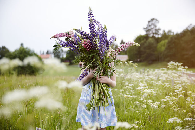 Low angle view of woman standing on purple flowering plant