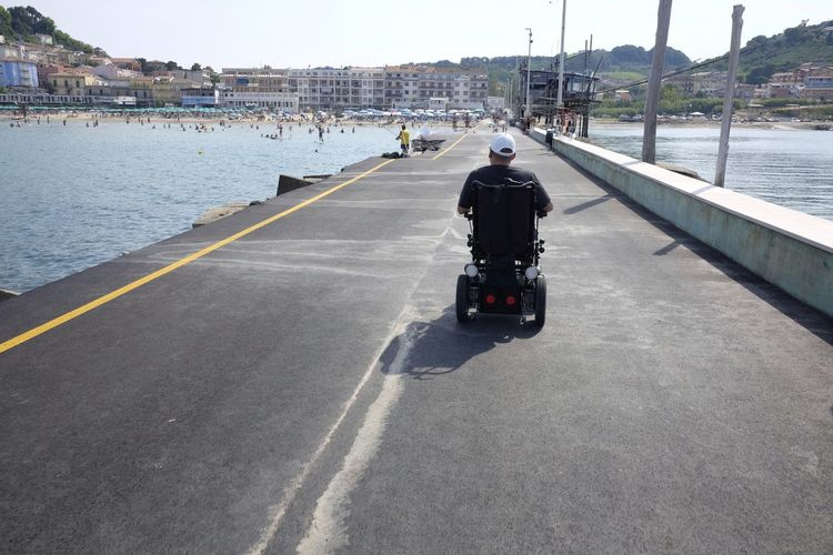 Electric wheelchair on the tourist pier Beach Day Disability  Disabled Electric Handicap Indipendence One Person Outdoors People Pier Scooter Transportation Weelchair