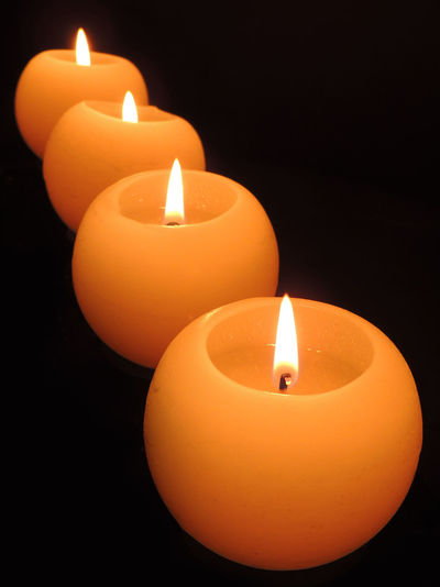 Lit candle in dark room