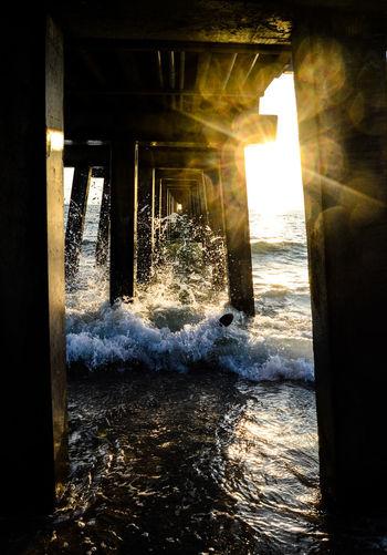 Waves Crash Under The Pier Pier Under The Pier Sunset Waves Crashing Waves  Light And Shadow Sunlight Architecture Sky Close-up Sun Sunbeam Solar Flare Evening