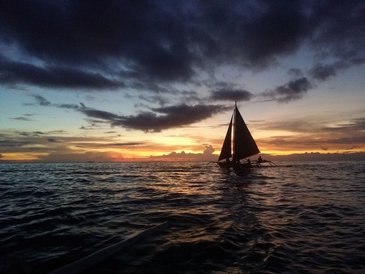 Silhouette Sailboat Sailing In Sea Against Sky At Sunset