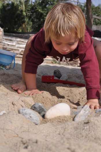 Blond Hair Boys Childhood Day Front View Full Length Fun Leisure Activity Lifestyles Looking Down One Boy Only One Person Outdoors People Playing Real People Sand Sand Pail And Shovel