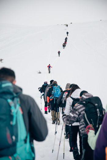 People skiing on mountain during winter