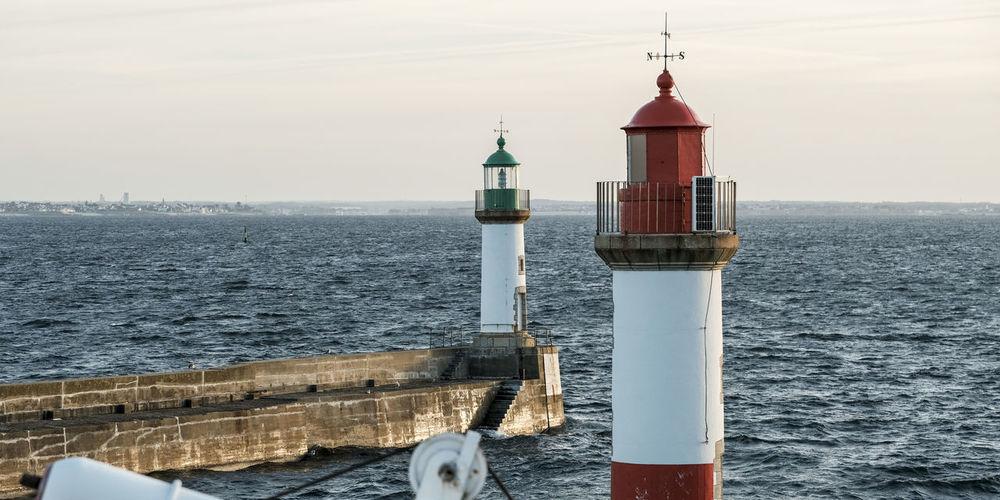 Lighthouse on sea by building against sky