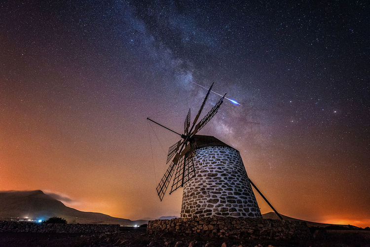 Low angle view of traditional windmill against sky at night