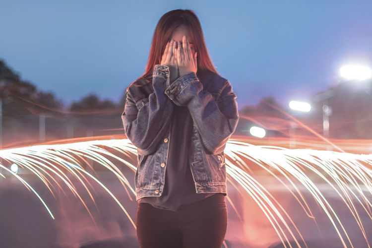 Young woman standing by light painting