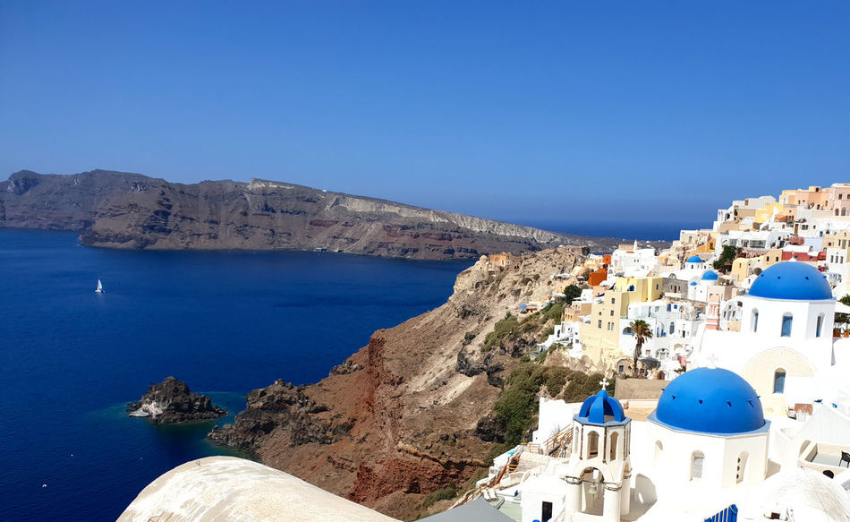 Aerial view of beautiful white washed buildings against blue sky, clouds and vivid sea in Santorini island, Oia, Greece Oia Santorini Oia Village Aerial View Architecture Blue Blue Dome Building Building Exterior City Clear Sky Copy Space Day Dome Mountain Nature No People Outdoors Sea Sky Tourism TOWNSCAPE Travel Travel Destinations Water White Washed Building