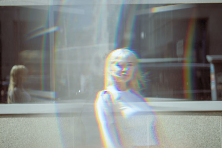 Double exposure of beautiful young woman standing in front of building
