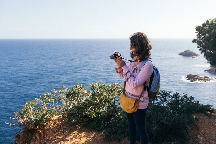 Side View Of Young Woman Photographing While Standing On Mountain Against Sea