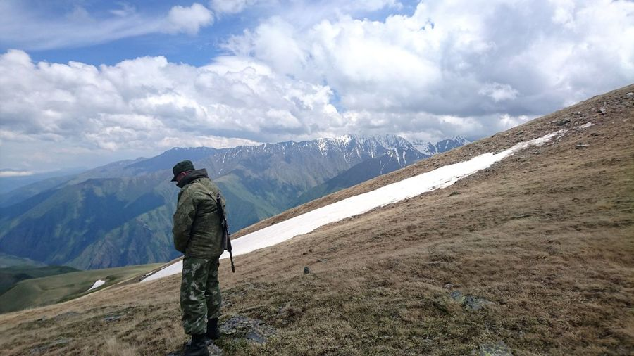 Side view of army officer standing on mountain against cloudy sky