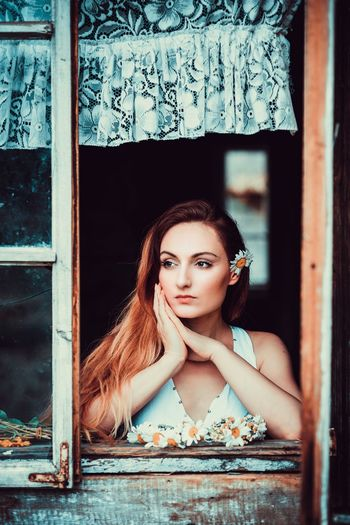 Portrait of young woman against window