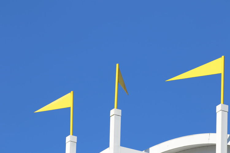 Architecture Blue Clear Sky Day Decoration Low Angle View Metal Flags No People Outdoors Roof Top Sky Yellow