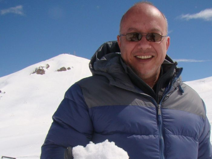 Portrait of smiling man in snow against sky