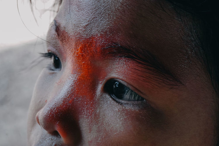 Close-up of young woman with wet face looking away