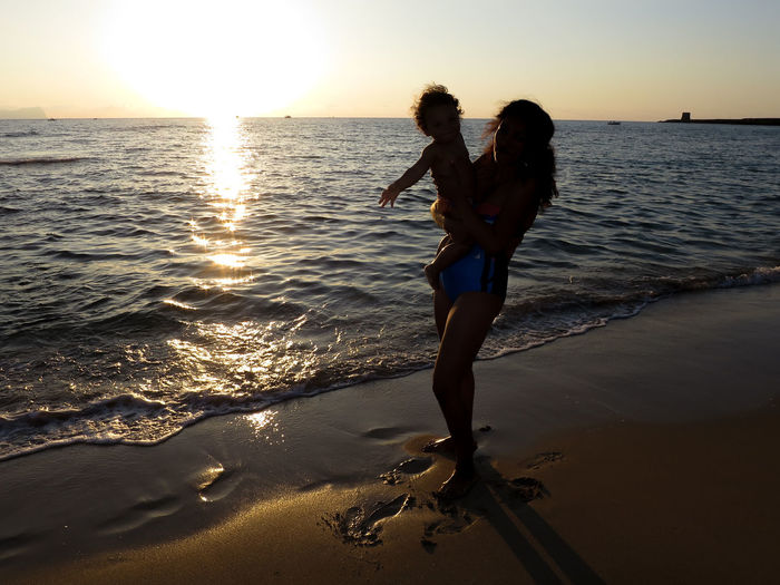 Silhouette mother carrying son while standing at beach during sunset against sky