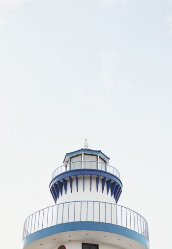 Low angle view of lighthouse on building against sky
