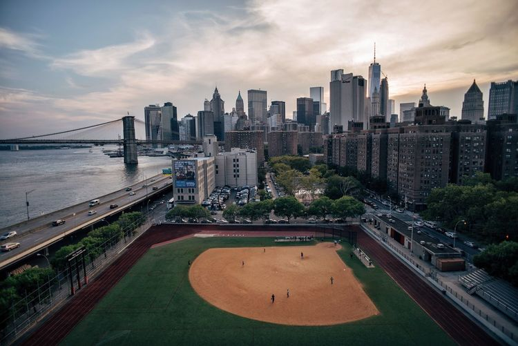 High angle view of baseball diamond by river in city against sky