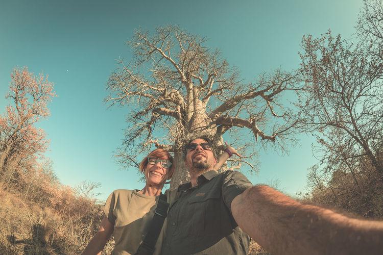 Portrait of man and woman taking selfie at savannah