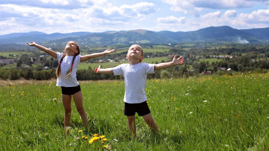 Happy friends enjoying on field against sky