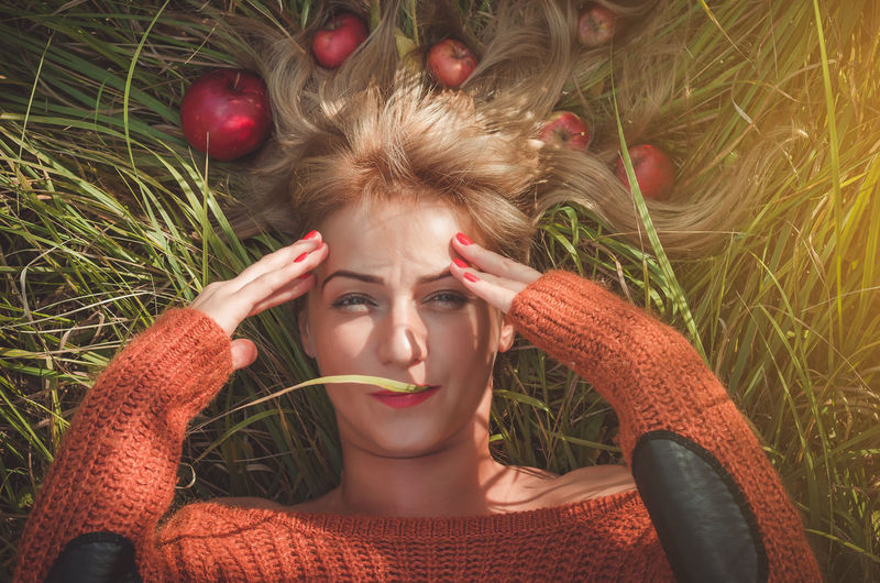 Woman laying on green grass with loose hair with apples Portrait One Person Plant Young Adult Beautiful Woman Lying Down Headshot Women Beauty Looking At Camera Young Women Front View Lifestyles Adult Leisure Activity Real People Emotion Nature Hair Hairstyle Outdoors Contemplation