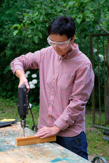 Carpenter using drill outdoors