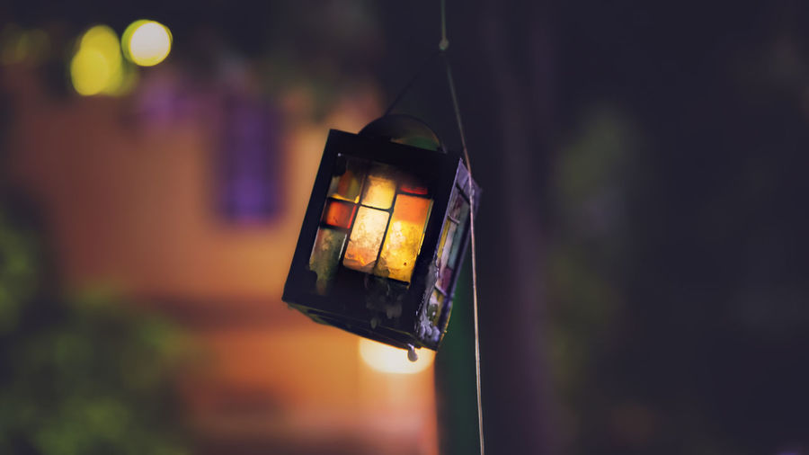 Close-Up Of Lit Lantern Against Blurred Background