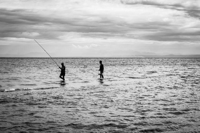Silhouette people fishing in sea against sky
