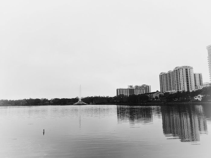 Scenic view of lake by buildings against clear sky