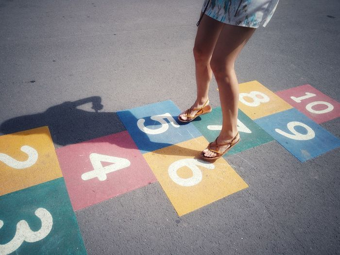 Low section of woman playing on hopscotch