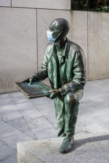Statue of man working on footpath