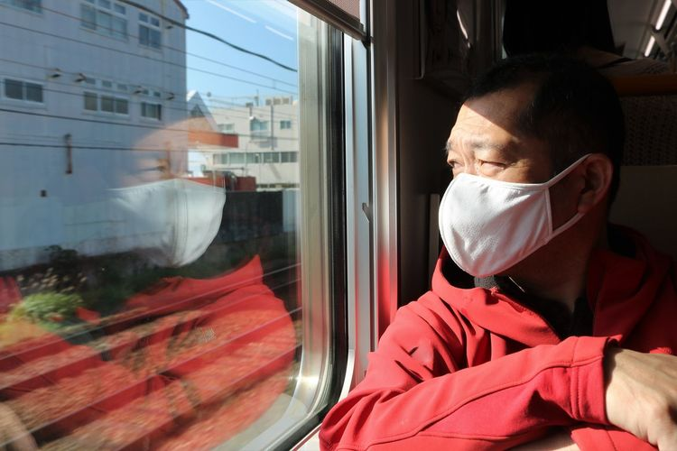 Man wearing mask looking through train window